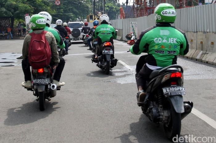 Driver Go-Jek mengantar penumpang. Foto: Lamhot Aritonang