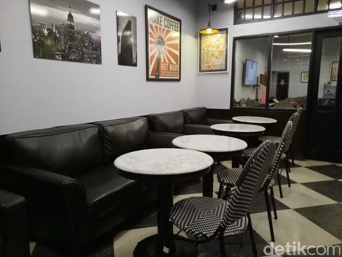 Jajaran sofa yang empuk dengan warna merah dan putih membuat desain kafe ini terlihat maskulin.