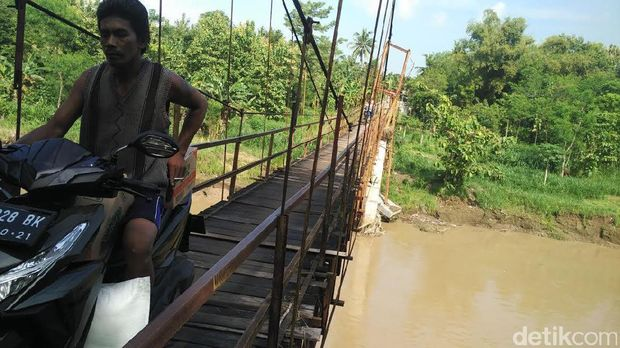 Warga tak memperhitungkan mengindahkan keselamatan jiwanya dengan tetap melintasi jembatan gantung Nambangan yang nyaris ambruk.