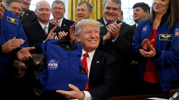 Trump menerima jaket NASA usai menandatangani RUU NASA di Ruang Oval