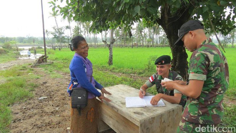 Ada portal dan meja tempat anggota TNI memeriksa pelintas batas. Seorang ibu tertawa sambil berbincang dengan petugas TNI (Fitraya/detikTravel)