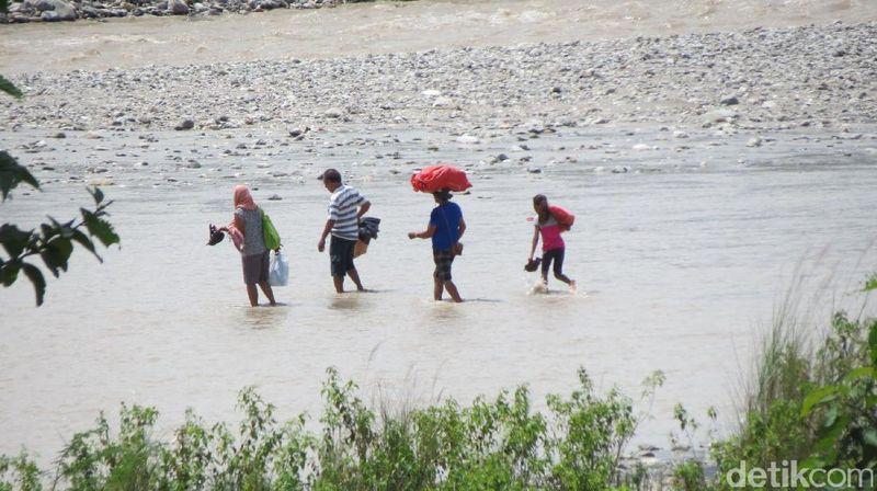 Warga Timor Leste yang pulang dari berbelanja di pasar perbatasan. Mereka kembali harus menempuh bahaya menyeberang Sungai Malibaka selebar 100 meter yang sebagian cukup dalam sampai sepinggang (Fitraya/detikTravel)
