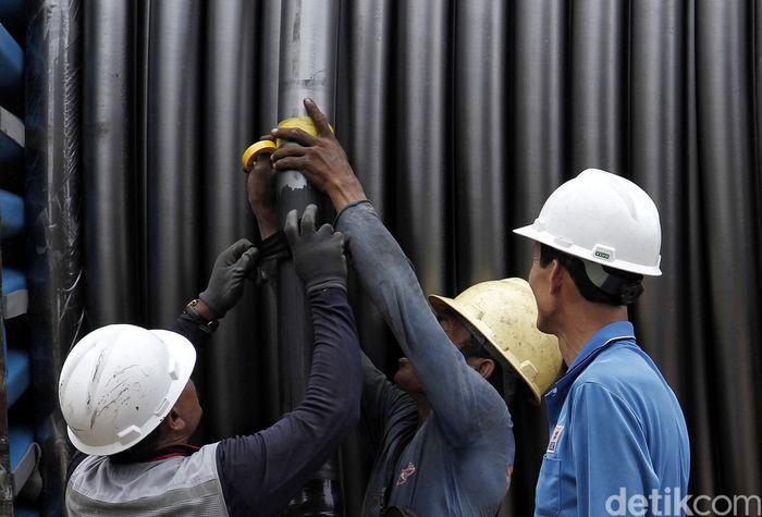 Pekerja menutup potongan kabel menggunakan solatif.