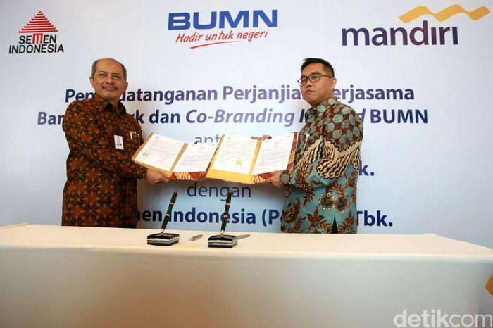 Direktur SDM dan Hukum PT Semen Indonesia Agung Yunanto (kiri) dan Direktur Digital Banking & Techology Bank Mandiri Rico Usthavia Frans (kanan) menunjukkan naskah kerja sama yang telah ditandatangani.