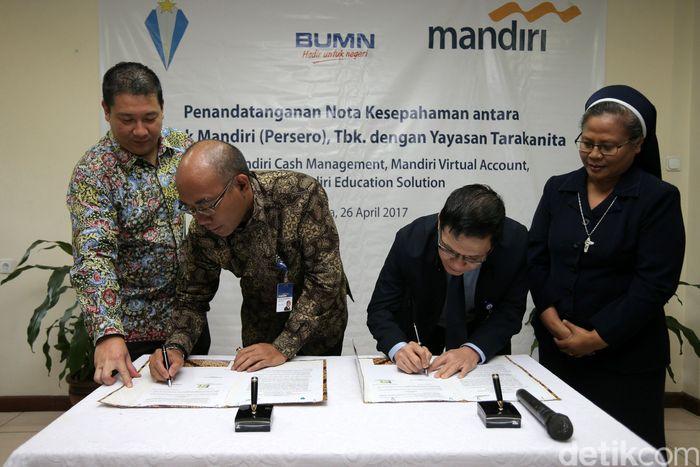 SVP Commercial Banking Bank Mandiri Dadang Ramadhan P dan bendahara yayasan Tarakanita Rafael Kristoforus Abdisa menandatangani naskah kerja sama.