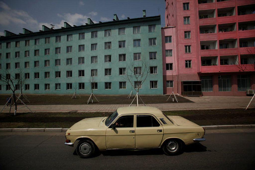 Sebuah mobil jadul di jalan raya Pyongyang melewati kompleks apartemen. Foto: Reuters