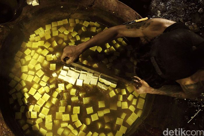 Tahu dimasukkan ke dalam tungku panas yang di dalamnya telah terdapat air kunyit. Air kunyit berfungsi sebagai pengganti formalin dalam produksi tahu. Dan proses ini yang sekaligus memberi warna kuning terhadap tahu. Pool/Muamar Khalid Affandi.