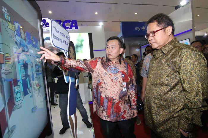 Direktur PT Bank Central Asia Tbk (BCA) Santoso memperkenalkan terobosan baru VIRA atau Virtual Assistant Chat Banking BCA kepada Menteri Komunikasi dan Informatika Rudiantara di pameran Teknopolis 2017. Pool/BCA.