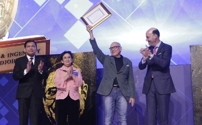 Peter F. Gontha mengangkat piagam usai menerima penghargaan dalam kategori Community Involvement sebagai alumni Citi. Foto: dok. Citi Indonesia