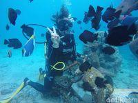 Naik motor di bawah air sambil bermain dengan ikan