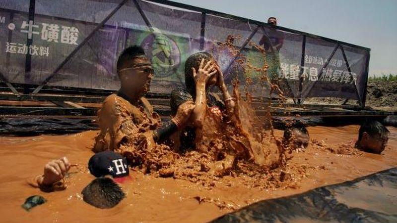 Akhir pekan lalu (15/7) baru saja diselenggarakan acara olahraga rutin Mud Run di Shanghai, China . Para peserta pun diharuskan untuk lari dan basah-basahan di kubangan lumpur (Aly Song/Reuters)