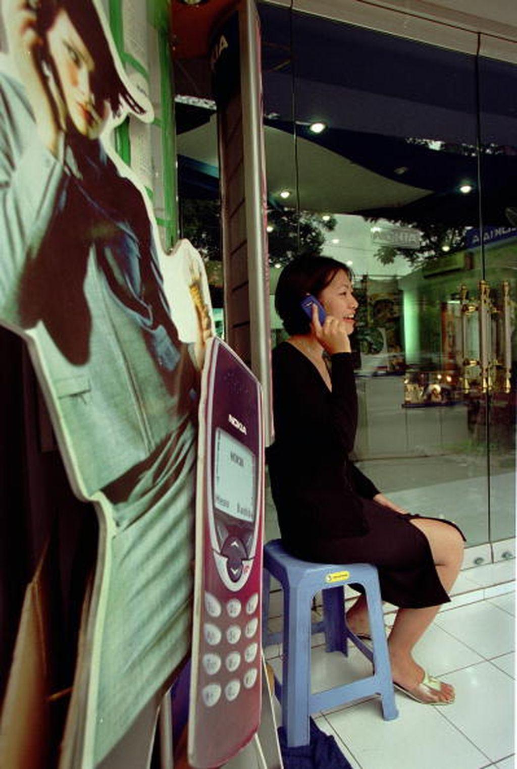 Dari foto yang diambil tahun 2000 ini, tampak seorang wanita asyik menggunakan ponsel di toko Nokia. Foto: Getty Images