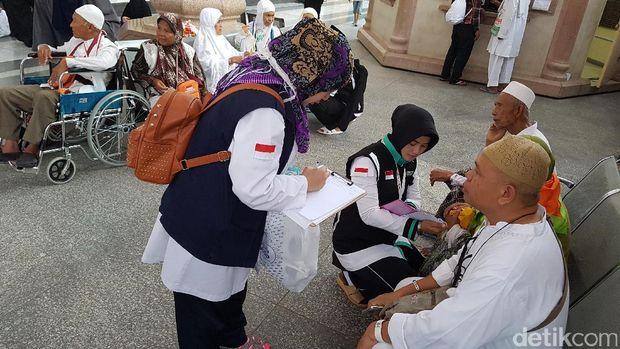 Serma Rizqy Kamila (duduk) melayani jemaah haji.