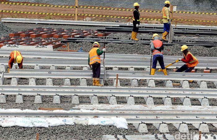 Pekerja tengah memasang rel MRT.
