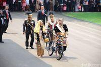 Oso menuntun hadiah sepeda. Di belakangnya ada kapolri dan istrinya yang juga menuntun sepeda.
