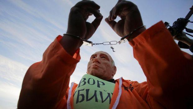 Salah satu demonstran memakai topeng Putin dalam unjuk rasa di St Petersburg