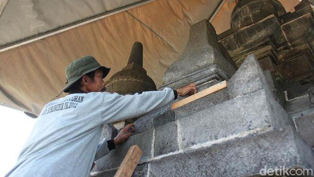 Petugas menambal batuan Candi Pawon