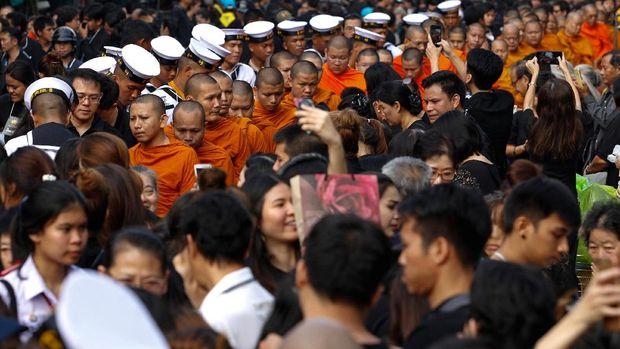 Warga yang masih berkabung memberikan sedekah kepada para biksu