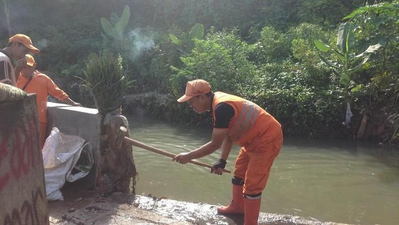 Pasukan Oranye Bangun Tanggul Sementara - Jakarta Sejumlah petugas Pekerja Penanganan Sarana dan Prasarana Umum atau pasukan dikerahkan membersihkan sampah sisa banjir di RT