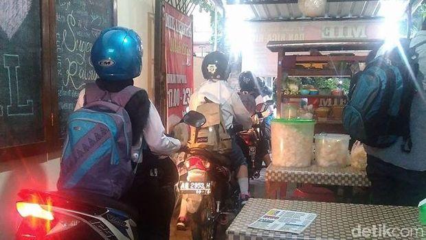 Foto pemotor lewat warung yang jadi viral.