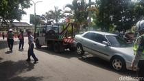 Parkir di Jalur Searah, Mobil Sedan Ini Terpaksa Diderek Petugas
