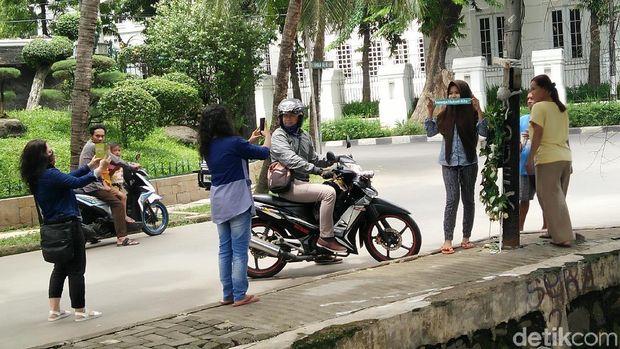 Warga yang melintas juga menyempatkan berhenti di tiang itu.