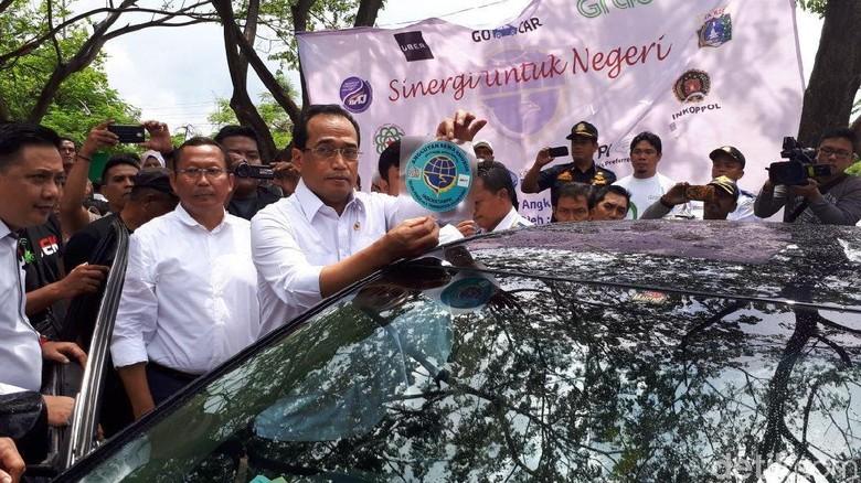 Masuk Mobil, Menhub Tempel Stiker di Kaca Belakang Taksi Online