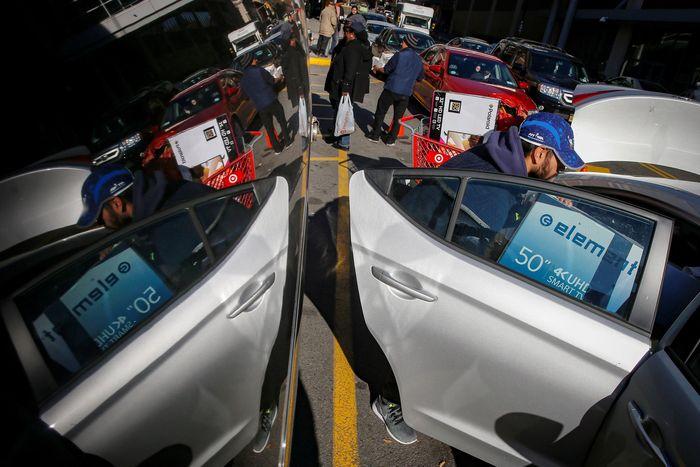 Seorang pria memasukkan barang hasil buruan di black friday ke mobil. Reuters/Brendan McDermid.