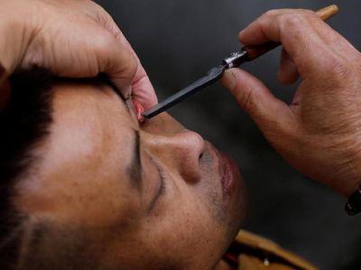 Foto: Atraksi Ekstrem Bersihkan Mata Pakai Pisau, Baca Kalau Berani