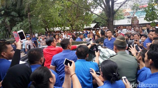 Jokowi memberikan kaos ke warga sebelum meninggalkan lokasi.