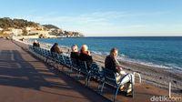 Turis yang duduk-duduk di bangku biru di pinggiran pantai Nice (Afif Farhan/detikTravel)