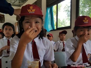 Hap! Menyuap bubur kacang hijau sambil tersenyum manis. Bubur ini merupakan makanan tambahan yang diberikan kepada siswa SD Barawanu, Nias Selatan, dalam program Tango Peduli Gizi Anak Indonesia. (Foto: Nurvita Indarini)