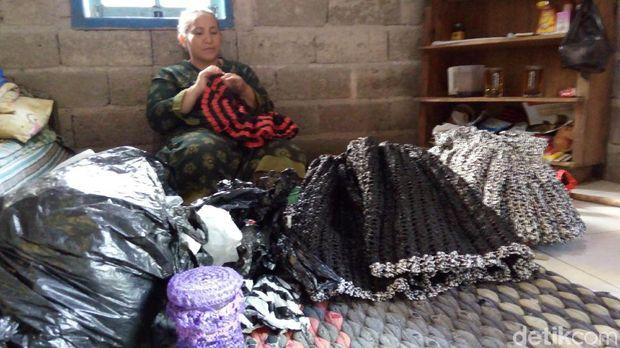 Agung Surtikanti sedang mengerjakan pakaian dari limbah plastik.