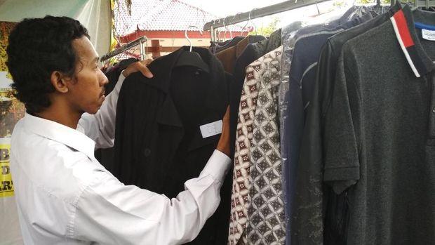 Calon pembeli sedangmemilih baju wabup yang hendak dibeli