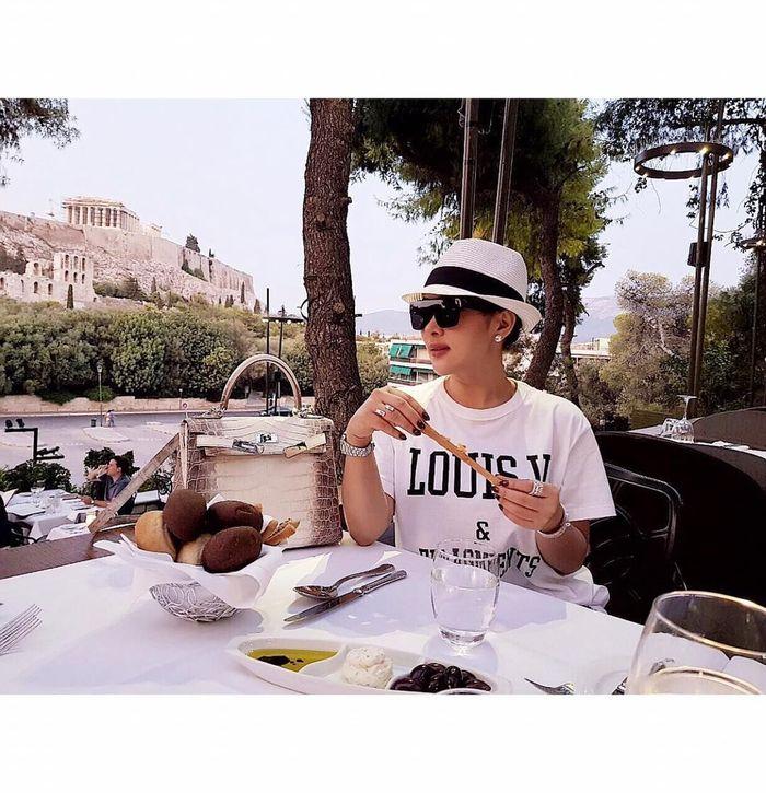 Ketika plesir ke Yunani, Syahrini menyampatkan makan cantik. Dengan outfit kasual dilengkapi topi dan kacamata hitam, Inces tampak menggenggam sepotong cheese stick. Foto: Instagram @princessyahrini