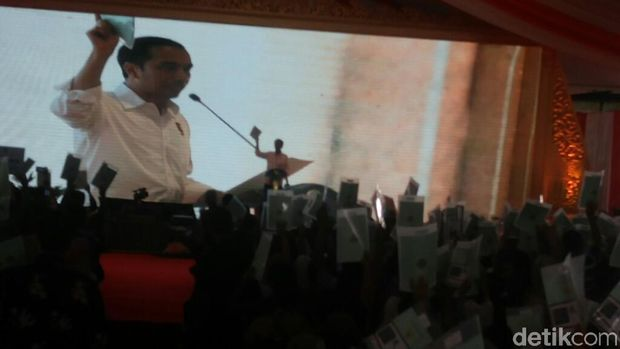 Jokowi meminta warga yang telah menerima sertifikat untuk mengangkatnya, kemudian dihitung.