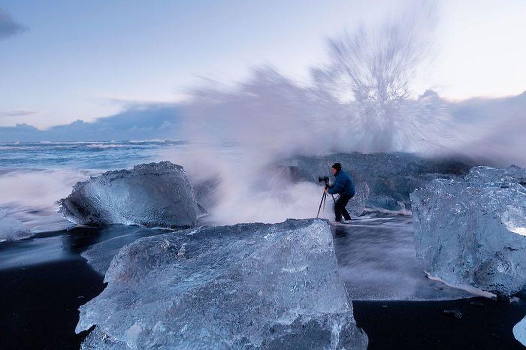 Tetap berdiri dengan kameranya meski diterjang badai ombak. (Foto: Internet)