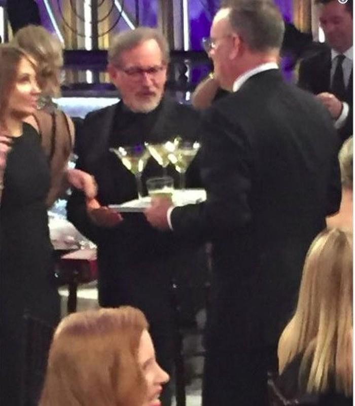 Tom Hank beralih profesi menjadi waiters? Tidak, Ia hanya membawa nampan berisi martini dan menuju ke mejanya.