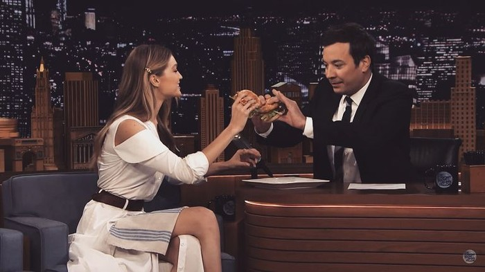 Dalam acara The Tonight Show bersama Jimmy Fallon, Gigi asyik menikmati burger. Ia bahkan melakukan tos burger bersama presenter kocak ini. Foto: Instagram gigihadid