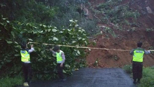 Polisi memasang police line di jalan yang tertimbun longsor