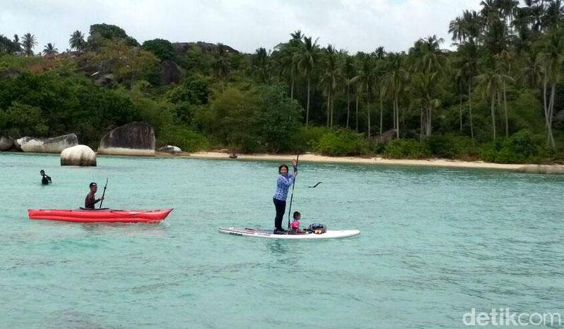 Di sela kunjungan kerja di Natuna, Kepulauan Riau, Minggu (28/1) Susi Pudjiastuti bermain paddle board di Pantai Batu Sindu. Ia tidak paddle board sendirian, melainkan bersama anak dan cucunya (Hendra Kusuma/detikTravel)