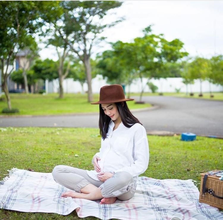Wih, cantiknya bumil pakai kemeja putih dan topi. (Foto: Instagram @ririndwiariyanti)