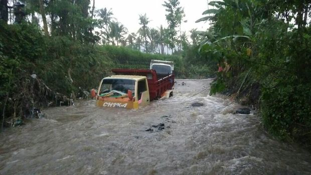 2 Dump truk terjebak di sungai yang berarus deras