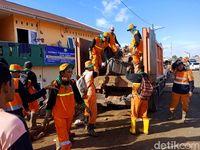 Petugas berjibaku bersihkan sampah sisa banjir di Kampung Pulo Description