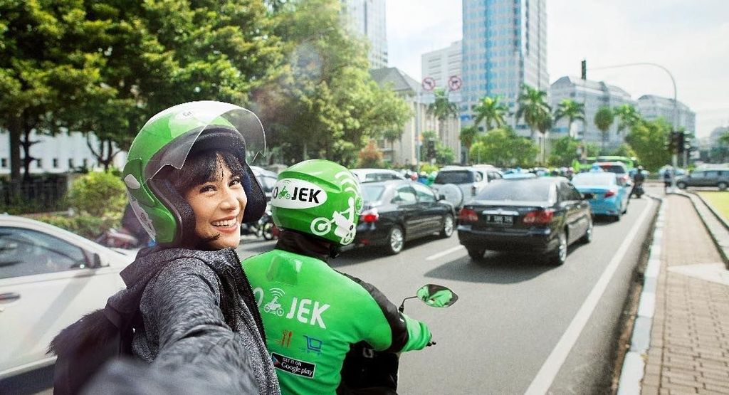Aktris Dian Sastrowardoyo memamerkan dirinya yang sedang naik Go-Jek.
