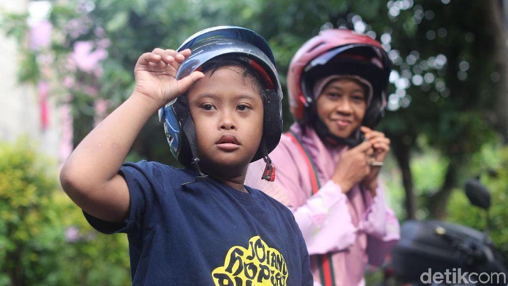 Ini Trik Suhartini Agar Anaknya Mau Duduk Manis di Motor