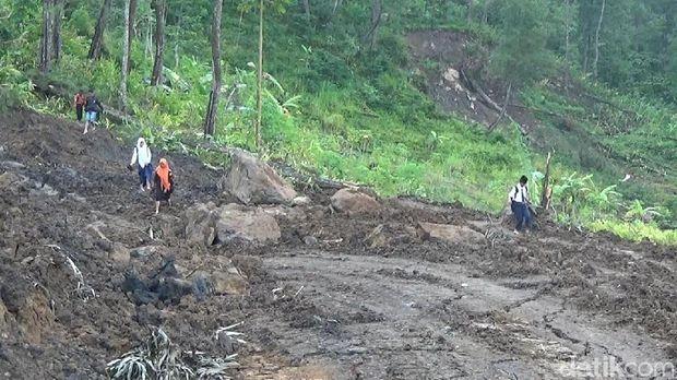 Warga tampak melalui jalan yang amblas di Banjarnegara.