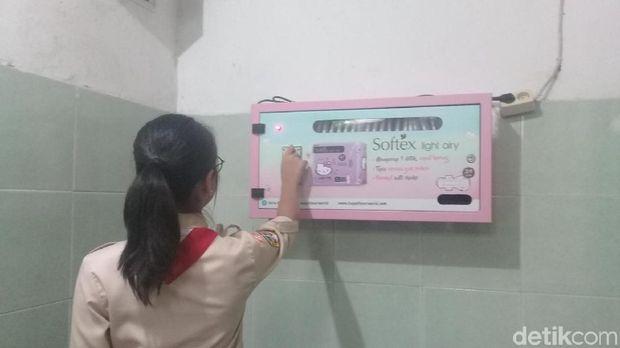 Seorang siswi memasukkan koin ke dalam vending machine pembalut di toilet putri SMPN 115.