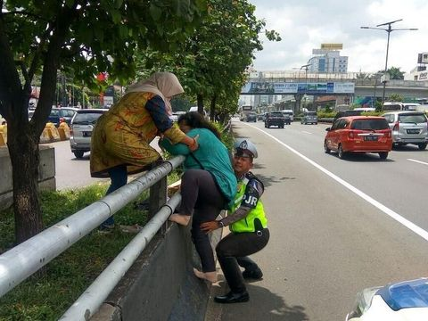 Polisi bantu emak-emak manjat.