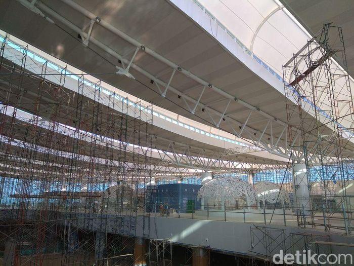 Proses pembangunan bandara masih terus berlanjut. Di bagian luar gedung terminal bandara masih terlihat besi-besi konstruksi yang sedang diselesaikan.